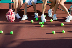 Scattered tennis balls on tennis court by feet of familyの写真素材 [FYI03627007]