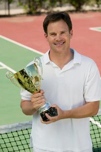 Man Holding Tennis Trophy net on tennis court  portraitの写真素材 [FYI03627016]