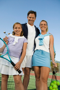Family on Tennis Court standing by net  portrait  low anglの写真素材 [FYI03627020]