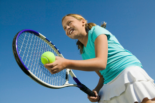 Young girl on tennis court Preparing to Serve  low angle vの写真素材 [FYI03627026]