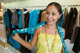 Girl Trying on Sequin Boa in clothing storeの写真素材 [FYI03627032]