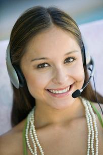 Young woman on sofa wearing phone headset  portraitの写真素材 [FYI03627103]