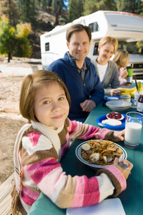 Girl eating at picnic table with family in campgroundの写真素材 [FYI03627139]