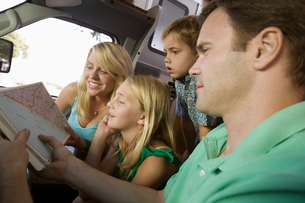 Family in RV Looking at Road Mapの写真素材 [FYI03627149]