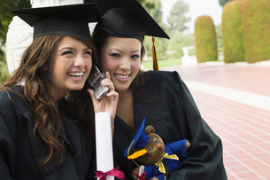 Two graduates using cell phone outsideの写真素材 [FYI03627172]