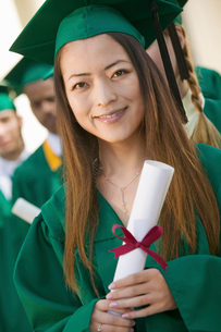 Graduate Holding Diploma outside with others behind  portrの写真素材 [FYI03627178]