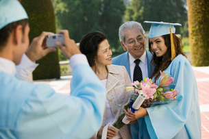 Graduate taking picture of other graduate and grandparentsの写真素材 [FYI03627185]
