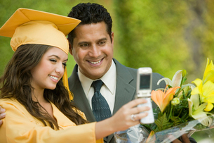 Graduate and father taking picture with cell phone outsideの写真素材 [FYI03627189]