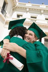 Two graduates hugging outside universityの写真素材 [FYI03627202]