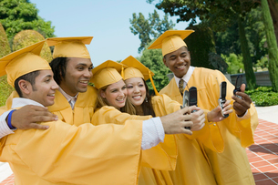 Group of graduates taking pictures with cell phone outsideの写真素材 [FYI03627205]