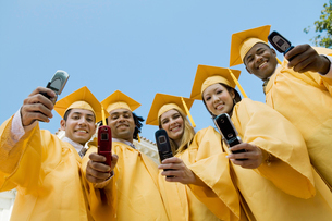 Group of graduates taking pictures with cell phone outsideの写真素材 [FYI03627207]