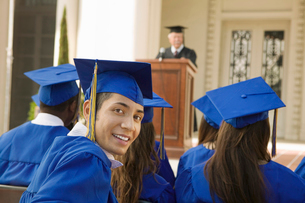 Graduates listening to speaker outsideの写真素材 [FYI03627209]