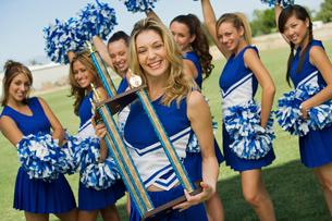 Smiling Cheerleader holding trophy  (portrait)の写真素材 [FYI03627225]