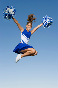 Smiling Cheerleader jumping in mid-air  (portrait)  (low aの写真素材 [FYI03627231]