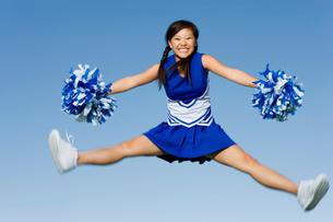 Smiling Cheerleader jumping in mid-air  (portrait)の写真素材 [FYI03627238]