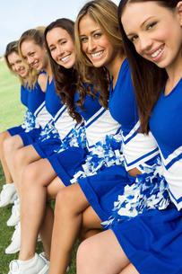 Cheerleaders sitting on bench  (portrait)の写真素材 [FYI03627243]