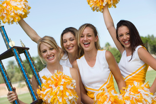 Smiling Cheerleaders holding trophy and pom-poms  (portraiの写真素材 [FYI03627248]