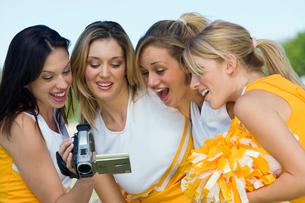 Cheerleaders watching video on video cameraの写真素材 [FYI03627250]