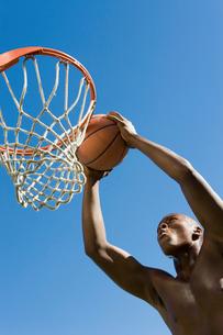 Basketball player slum dunking ball  low angle viewの写真素材 [FYI03627264]