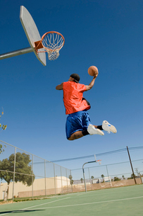 Basketball player  mid-air  dunking ball  side viewの写真素材 [FYI03627267]