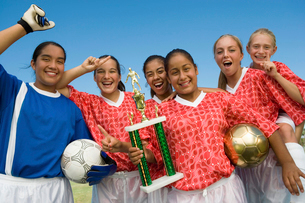 Girls soccer team (13-17) holding trophy and celebratingの写真素材 [FYI03627270]