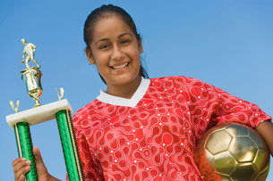Girl (13-17) in soccer kit holding trophy and ball  portraの写真素材 [FYI03627281]