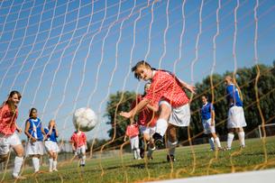 Girl (13-17) scoring with soccer ballの写真素材 [FYI03627286]