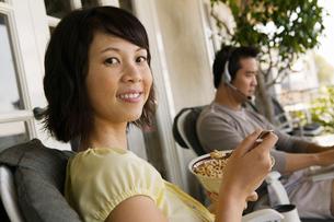 Woman having breakfast on porch  man using laptop in backgの写真素材 [FYI03627345]