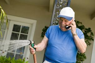 Senior man watering lawn  talking in mobile phoneの写真素材 [FYI03627353]