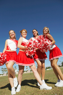 Cheerleaders with Pom-poms standing on football field  lowの写真素材 [FYI03627407]