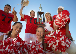 Football players and cheerleaders hoisting trophy  low angの写真素材 [FYI03627412]