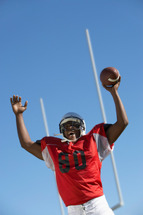 Football Player cheering with ball on field  low angle vieの写真素材 [FYI03627414]