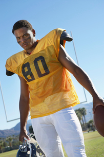 Football player holding helmet and ball standing on fieldの写真素材 [FYI03627415]