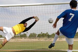 Goalkeeper reaching for ball as soccer player scoresの写真素材 [FYI03627425]