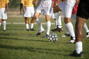 Soccer players competing for ball  low sectionの写真素材 [FYI03627427]