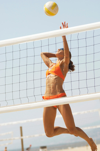 Female beach volleyball player jumping to spike volleyballの写真素材 [FYI03627446]