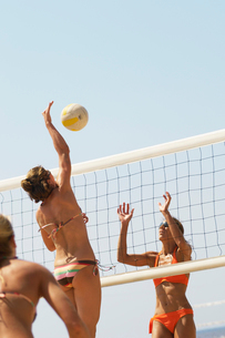 Beach volleyball player jumping to spike volleyball over nの写真素材 [FYI03627449]