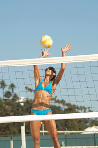 Female beach volleyball player jumping to spike volleyballの写真素材 [FYI03627452]