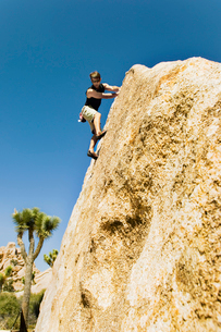 Woman Free Climbing on Cliff  side viewの写真素材 [FYI03627456]
