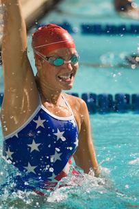 Female swimmer celebrating victory in poolの写真素材 [FYI03627498]