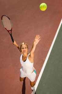 Woman on tennis court Serving Tennis Ball  elevated viewの写真素材 [FYI03627531]