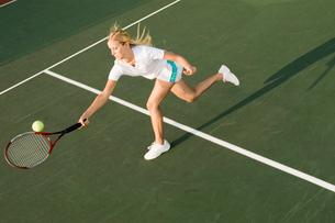 Tennis Player Reaching to hit tennis ball on tennis courtの写真素材 [FYI03627558]