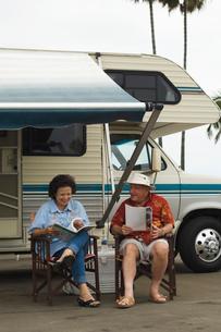Couple relaxing outside motor homeの写真素材 [FYI03627584]