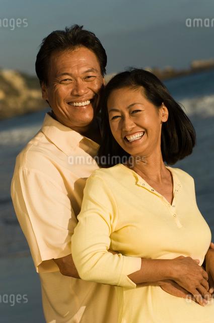 Couple embracing on beach  (portrait)の写真素材 [FYI03627616]