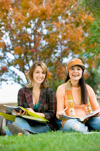 Two students studying outdoors  (portrait)の写真素材 [FYI03627710]