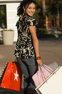 Young woman carrying shopping bags  outdoors  (portrait)の写真素材 [FYI03627780]