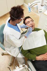 Dentist examining male patientの写真素材 [FYI03627815]