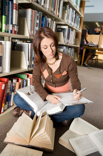 Female college student making notes in libraryの写真素材 [FYI03627842]
