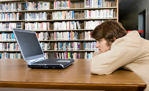 Bored male student with laptop at libraryの写真素材 [FYI03627854]