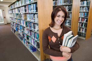 Female student holding books in libraryの写真素材 [FYI03627858]